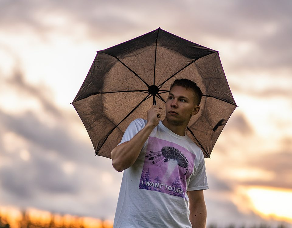 Man wearing I want to leave shirt and umbrella